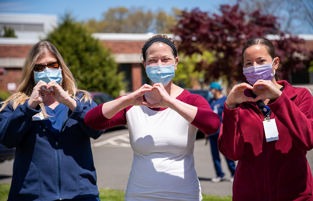 Three nurses standing outside in the sun wearing surgical face masks and holding their hands up in the shape of hearts